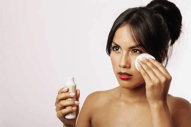 a woman applying skin care product